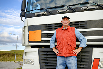 smiling truck driver in front of his semi | ELD for Truckers Aim to Improve Safety