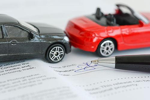 two toys cars in pretend accident on paperwork with a pen | Colorado Car Insurance Law
