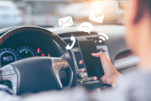 man holding phone while driving | Cell Phone Use and Car Accident Risk