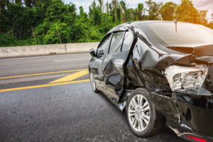 black compact car sideways on the highway | On-the-Job Car Accidents