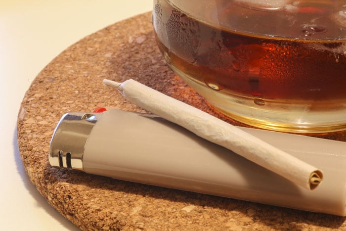 a joint laying on a lighter next to a glass of booze
