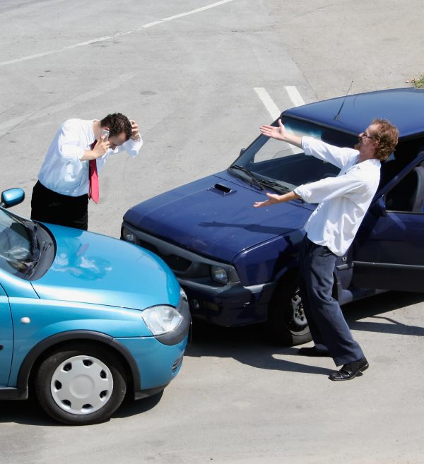 two upset people arguing after an accident