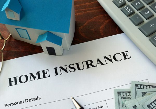 home insurance document on a desk with a keyboard a small house and money
