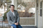 Greg Green of the Green Law Firm, P.C. sitting on a white porch while wearing a gray suit coat